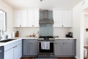 two-tone kitchen with gray lower cabinets, white uppers and tiled backsplash behind vent hood