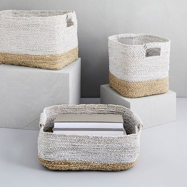 Woven storage baskets with handles in various sizes. Bottom 1/4 is beige and top 3/4 is light gray