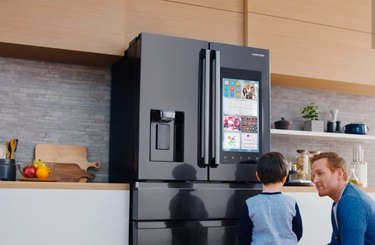 two figures in a kitchen in front of a smart refrigerator with a screen