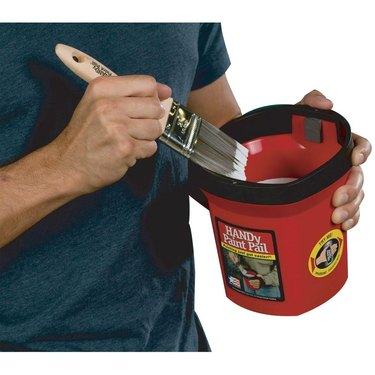 Dipping paint brush in paint container.