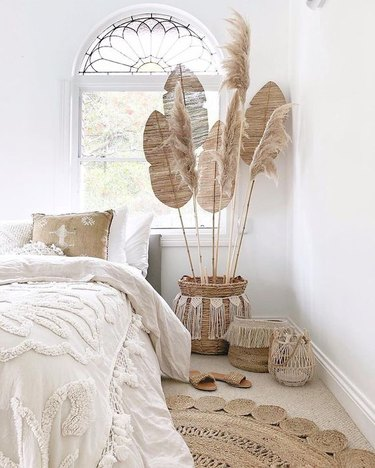white boho beach bedroom with beach fans and pampas grass