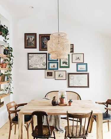 Dining room with minimal wood table and mismatched vintage wooden chairs and woven pendant light