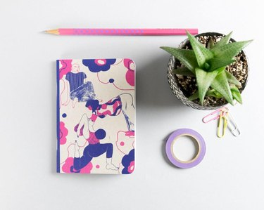 overhead view of notebook with pencil, other office supplies, and small plant