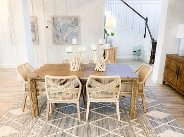 modern coastal dining room with woven chairs and driftwood candle holders
