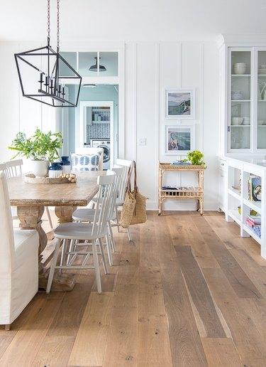 Light hardwood coastal flooring idea dining room with farmhouse table and chairs