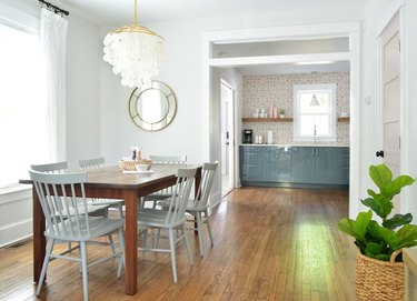 minimalist coastal dining room with capiz chandelier and blue windsor chairs