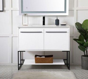 White Scandinavian bathroom vanity with black handles in white bathroom