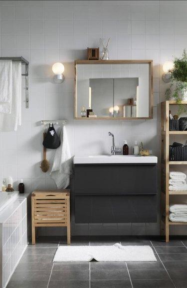 Gray Scandinavian bathroom vanity with dark gray vanity, large mirror, and wooden shelves