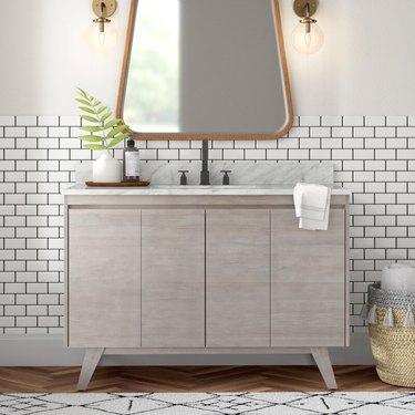 Gray, teak Scandinavian bathroom vanity in a white bathroom with subway tiles