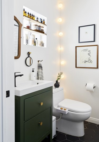 trending bathroom lighting in white bathroom with small green vanity
