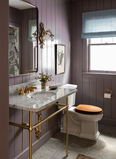 ornate gold trending bathroom lighting in bathroom with purple shiplap walls and marble sink