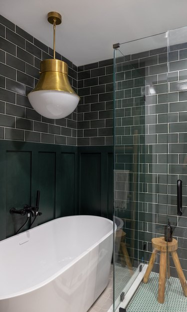 trending bathroom lighting in bathroom with dark green subway tiles and white tub