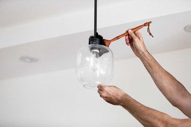 Man dusting hanging glass pendant light
