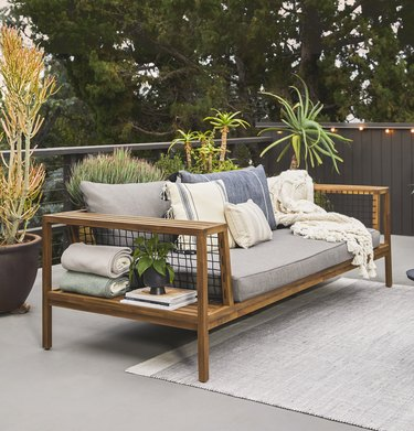 outdoor sofa with light rug and plants nearby