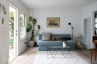 living room space with open door, blue couch, and black coffee table
