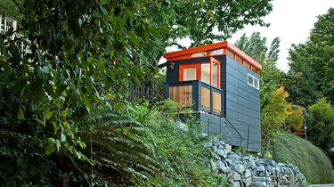 Modern shed painted orange and teal on hillside