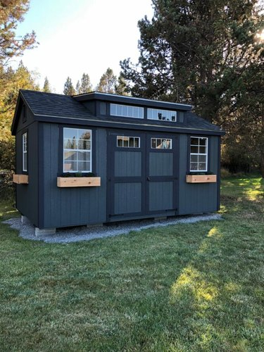 Modern shed painted black with wood flower boxes and transom windows