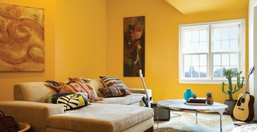 yellow family room paint colors with sectional couch and circle coffee table