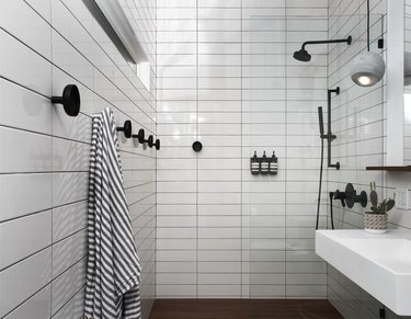 white subway shower tile ideas in bathroom with matte black fixtures and striped towel