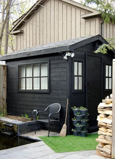 Modern shed painted black with potted plants and black chair