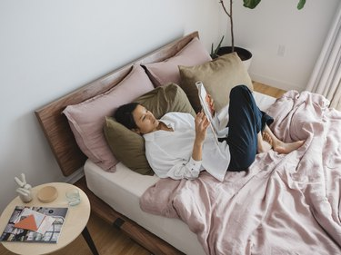 person on bed with multi-colored sheets and side table nearby