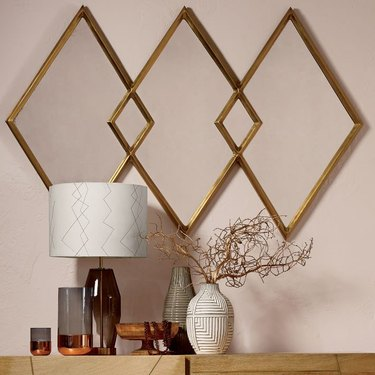 Minimalist entryway design with diamond mirrors mounted on wall beige wall above lamp and ceramics