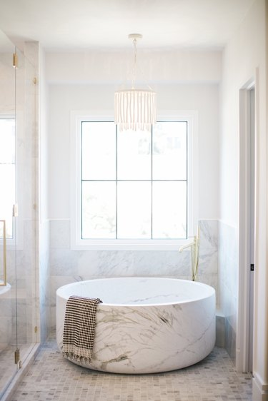 bathroom chandelier lighting idea with wood beaded fixture hanging over marble tub