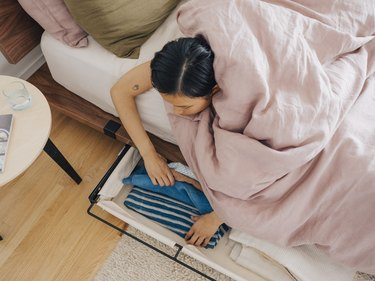 person in bed looking through underbed storage