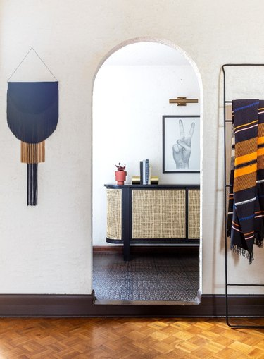 Minimalist entryway design with handmade wall decor and leaning ladder on outside of walkway and parquet floors