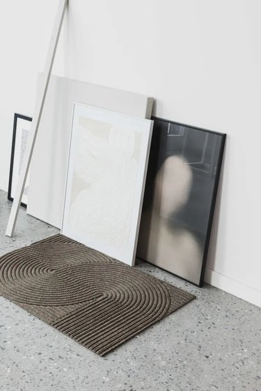 Minimalist entryway design with framed artwork against wall on confetti floor with decorative mat.