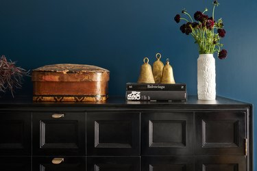 Minimalist entryway design with black cabinet with gold hardware against turquoise wall.