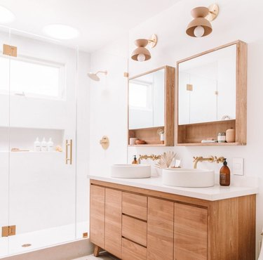 Feminine and minimalist bathrooms with standing shower and brass fixtures