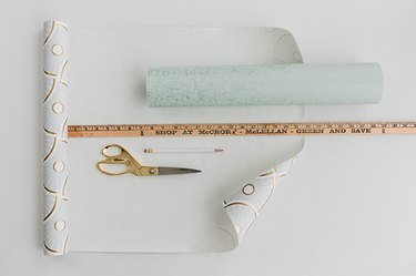 Measure and mark pieces of wallpaper for the sides and front of the cabinet.
