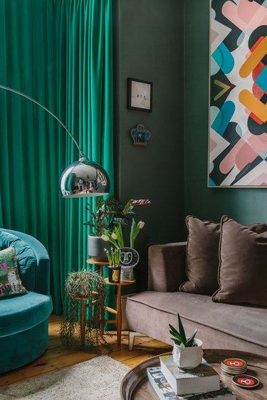 green living room with green velvet curtains and velvet sofa
