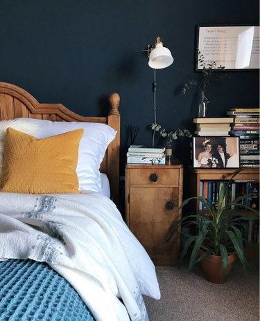 White industrial clamp light on a navy-blue wall over a wooden nightstand