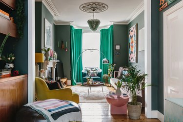 green living room with colourful furniture and large bay window