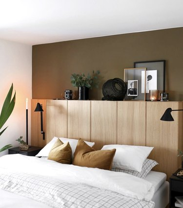 Unfinished wood cabinets used in place of a headboard on a mostly-white bed