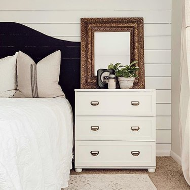 Off-white three-drawer dresser with a gold mirror and plant on top, next to a bed with a black headboard and white bedding