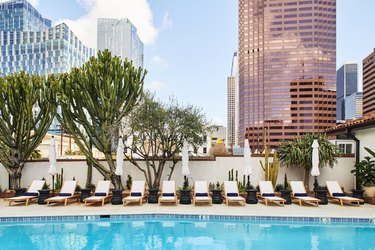 hotel pool with white chairs and city buildings in the background