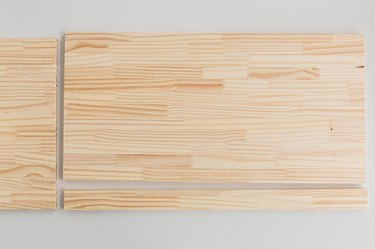 Cut the wood board to size so that it fits across the top of the cabinet.