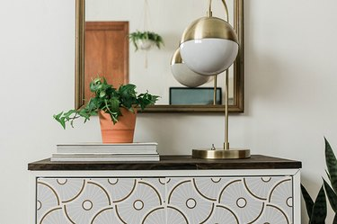 A vintage arched mirror adds more functionality when hung above an IKEA entry cabinet.