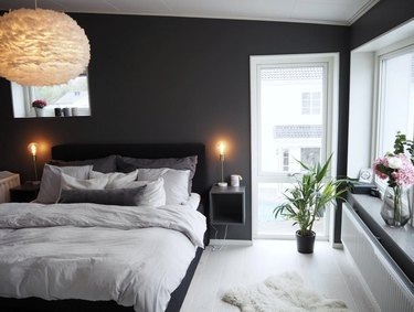 A small gray cubby mounted next to a bed of whites and cool grays, in a dark gray room