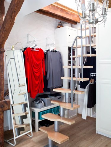 IKEA bedroom idea with a DIY closet made up of white storage brackets, and a freestanding mirror. Open stairs are in front of the clothes