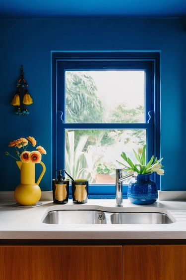 bright blue kitchen with sink area and yellow vase