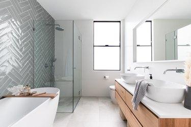 minimalist bathroom vanity with two bowl sinks in in bathroom with herringbone tile