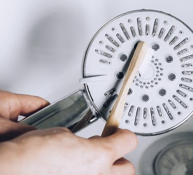 cleaning showerhead with toothbrush