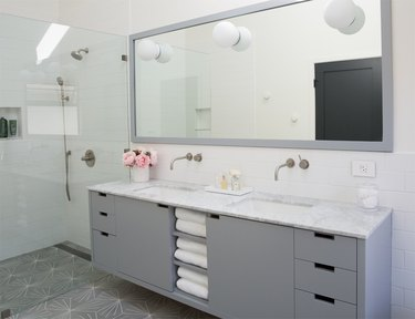 minimalist bathroom vanity with gray cabinets and large mirror