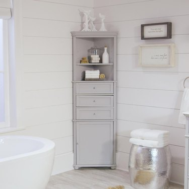 Gray corner bathroom cabinet with tub and wood-paneled walls, and wo