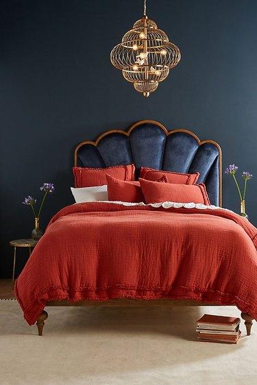 art deco furniture in anthropologie bedroom with crimson bedding