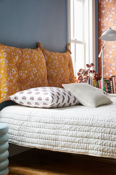 blue bohemian bedroom idea with yellow tufted pillow headboard